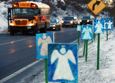 A bus travelling from Newtown, Conn., to Monroe stops in front of 26 angels along the roadside on the first day of classes for Sandy Hook Elementary School students since the Dec. 14 shootings.